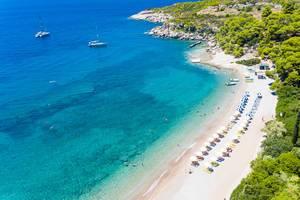 Luftbild von Touristen auf aufgereihten, gelben Sonnenliegen unter Sonnenschirmen, am Agii Anargiri Strand auf Spetses, am blauen Meer