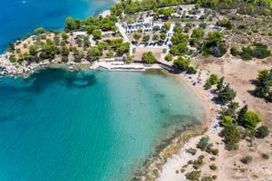 Luftbild zeigt Badegäste in einer blauen Bucht am Hinitsastrand in Porto Heli, Chinitsa