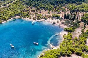 Luftbild zeigt das blaue Wasser des Argolischen Golfs vor dem Urlaubsstrand  Zogeria auf Spetses, Griechenland