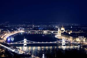 Luftbild zeigt die beleuchteten Brücken und historische Häuser an der großen Donau bei Nacht