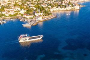 Luftbild zeigt ein Frachtschiff beim Verlassen des Hafens von Spetses, auf dem blauen Argolischen Golf in der Ägäis