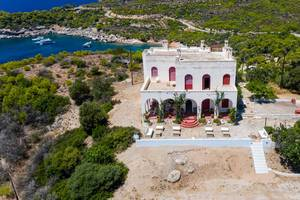 Luftbild zeigt ein mediterranes Wohnhaus auf der felsigen Insel Spetses, mit Blick auf den Strand Plaza Paraskevi