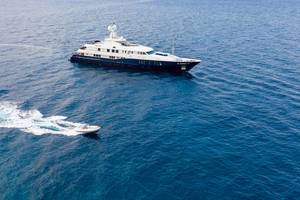 """Luftbild zeigt ein Sportboot beim Überholen der luxuriösen Turqoise Yachts Motoryacht """"Rare Find"""" auf dem Argolischen Meer, mit einem Innendesign von H2 Yacht Design"""