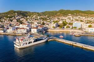 Luftbild zeigt eine Fähre mit Touristen beim Anlegen im Hafen von Spetses im Argolischen Golf, vor der Küste des Peloponnes, Griechenland