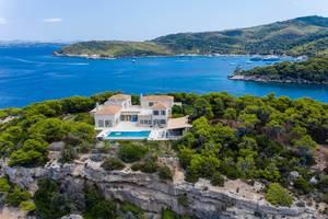 Luftbild zeigt eine mediterrane Villa mit Pool in der Natur, auf einer Felsenklippe der griechischen Insel Spetses