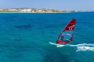 Luftbild zeigt einen Mann beim Windsurfen auf einem Surfbrett mit NCX Segel, der Kurs auf die griechische Insel Paros nimmt