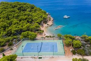Luftbild zeigt einen Tennisplatz am Zogeriastrand an der Felsenküste der Insel Spetses, Griechenland