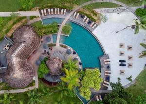Luftbild zeigt Nahaufnahme des Spabereichs mit blauem, runden Pool, Sonnenliegen und Bast-Sonnenschirm neben Palmen auf Mahé, Seychellen