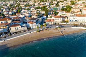 Luftbild zeigt Palmen am Küstenweg des Agios Mamas Strand, mit Häusern im Neoklassizismus-Stil, auf der kleinen Insel Spetses, im Argolischen Golf