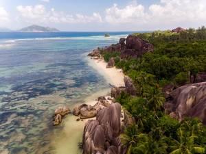 Luftbild zeigt Palmen, Granitfelsen und die Küste von La Digue und den Strand Anse Source d