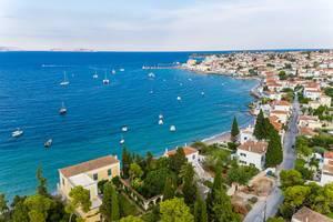 Luftbild zeigt Schiffe vor der griechischen Insel Spetses und griechische Kalksteinhäuser am Kaiki Strandweg