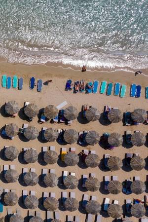 Luftbild zeigt Urlauber auf bunten Sonnenliegen von oben fotografiert und mediterrane Strandschirme