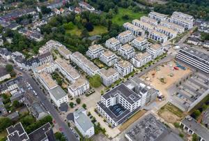 Luftbildaufnahme von neuen Mehrfamilienhäusern im Wohnquartier Park Linne, neben einer Baustelle in Köln Müngersdorf