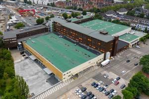 Luftbildfotografie eines Rewe Supermarkts mit grupnem Flachdach und Parkplatz an der Stolberg Straße 92 in Köln
