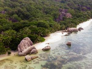 Luftfotografie des Ufers von Anse Union auf La Digue zeigt weißen Sandstrand und Tropenwald der Seychellen-Insel