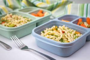 Lunchboxen mit Nudeln und Gemüse auf weißem Hintergrund