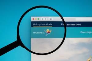 Lupe über Bildschirm akzentuiert Logo von Holiday in Australia, der Website für Reisen nach Australien