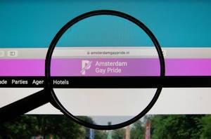 Lupe über Bildschirm betont Logo und Internetadresse der Amsterdam Gay Pride