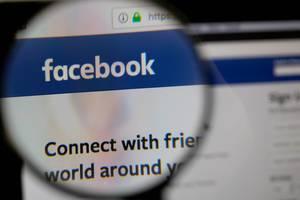 Lupe über dem Facebook-Logo auf dem Bildschirm