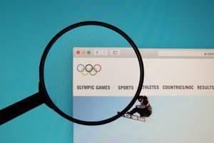 Lupe über dem Logo der Internetseite der Olympischen Spiele