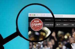 Lupe über dem Logo und Schriftzug der Internetseite von Visit New Orleans