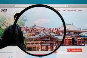 Lupe über der PC-Bildschirm mit Webseite von Visit Japan mit Infos zu Reisen nach Japan