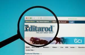 Lupe über Logo von Iditarod auf der Website zum längsten Hundeschlittenrennen der Welt in Alaska