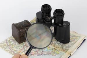 Lupe und Fernglas auf alter Landkarte