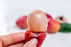 Lychee fruit pulp without peel in a woman