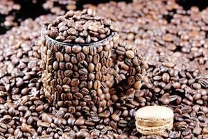 Macaron neben einer Tasse aus Kaffeebohnen mit Kaffeebohnen gefüllt und umgeben