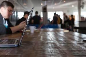 MacBook von der Seite fotografiert und Teilnehmer im Hintergrund