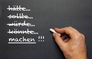 Machen!: Mann schreibt mit Kreide verschiedene konjunktive Verben auf eine Tafel - Nahaufnahme