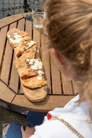 Mädchen betrachtet Knoblauchbrot auf dem Tisch
