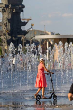 Mädchen fährt mit Roller an einem Springbrunnen vorbei