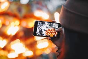 Mädchen fotografiert mit Smartphone in einem Vergnügungspark. Bunter, verschwommener Hintergrund