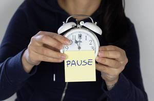 Mädchen hält Wecker mit Klebezettel mit Wort Pause in Händen