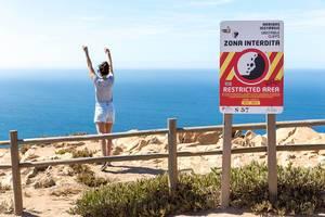 Mädchen hinter dem Geländer der Klippen am Cabo da Roca posiert für ein Foto