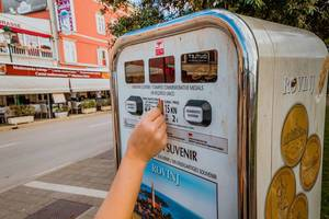Mädchen kauft Souvenir am Automaten in Rovinj, Kroatien