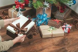 Mädchen legt ein Geschenk unter den geschmückten Weihnachtsbaum im Wohnzimmer