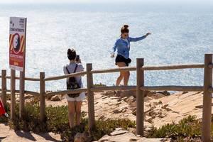 Mädchen machen waghalsige Fotos an den Klippen von Cabo da Roca