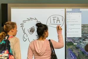 Mädchen schreibt auf einem großen Touchscreen mit Stylus-Unterstützung von Steelcase