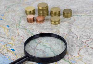Magnify glass with money on map