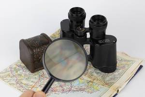 Magnifying glass and binoculars on old map