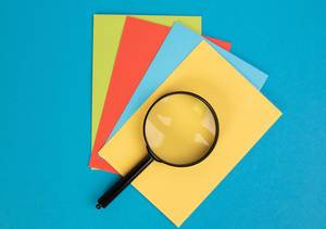 Magnifying glass on colorful papers