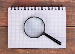 Magnifying glass on notepad
