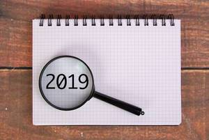 Magnifying glass over 2019 written in notebook