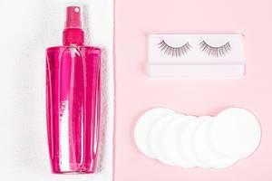 Make-up Entferner auf einem weißen Handtuch, Abschminkpads und künstliche Wimpern, Aufnahme von oben auf rosa Hintergrund