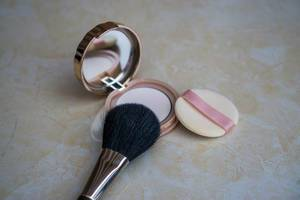 Makeup Brush laying on Powder Box with Mirror