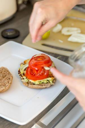 Making halloumi-cheese burger with avocado and tomato