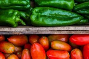 Makroaufnahme von grünen Paprikas und Roma Tomaten in Holzkisten